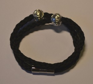 Pyntet med et par perler og lukket med pålimet magnetlås.